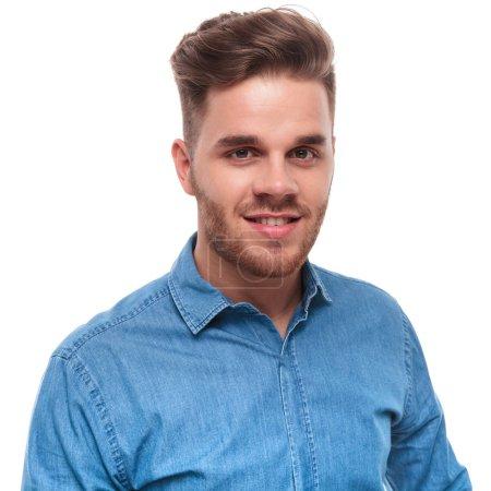 Photo pour Portrait d'attrayant jeune homme décontracté en chemise bleue, debout sur fond blanc - image libre de droit