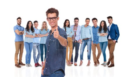 Photo for Casual man wearing glasses with young team behind makes ok sign while standing on white background with a hand in pocket - Royalty Free Image
