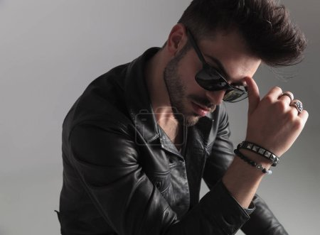 portrait of pensive man with sunglasses and black leather jacket looking down to side and resting his head in his thumb