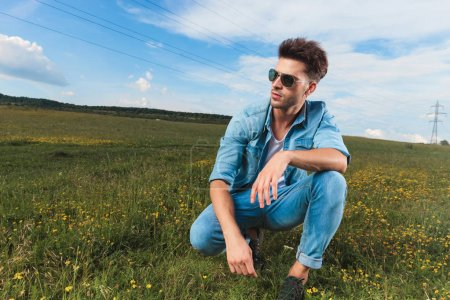 casual man wearing sunglasses and undone blue shirt kneeling on a hill outside and looking to side