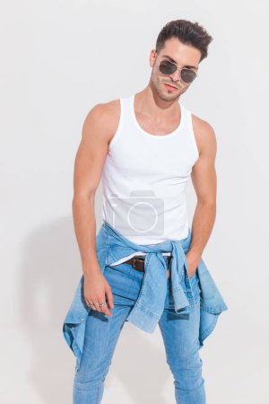 portrait of seductive casual man with denim shirt around waist standing with a hand in pocket in spotlight near a white wall. He is wearing a pair of sunglasses and jeans