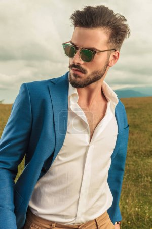 Photo for Casual man in blue suit looking to side while standing outside in a grass field, with clouds in the sky in background - Royalty Free Image