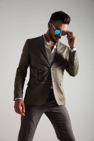 portrait of stylish man fixing sunglasses and looking down while standing on light grey background