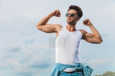 sexy man in white undershirt and sunglasses flexing his biceps outside and looking up to side
