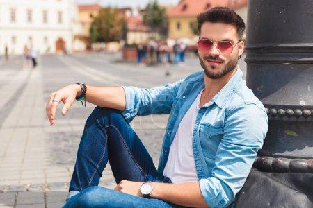 Photo pour Portrait d'un bel homme souriant assis sur une rue piétonne près d'un poteau d'éclairage avec la main posée sur son genou - image libre de droit