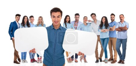 young casual team leader holding two empty speech bubbles while standing in front of his team