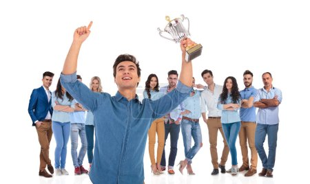 successful casual team with young leader celebrating in front while holding a trophy and a hand in the air