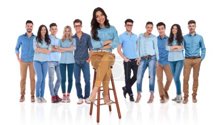 Photo pour Heureux équipe occasionnelle avec leur jeune femme leader assis sur une chaise en bois devant eux avec les mains croisées - image libre de droit