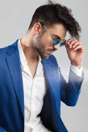 portrait of smart casual man fixing his sunglasses looking down to side while standing on light grey background