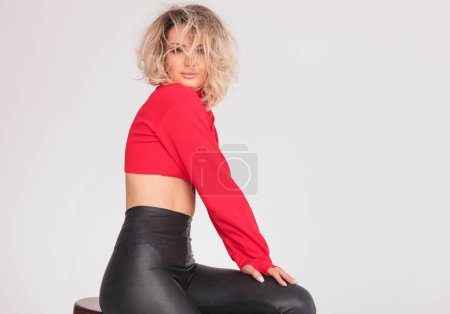 side view of attractive woman in red top with blonde messy hair sitting on wooden chair