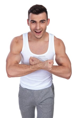 Photo for Portrait of excited man in undershirt flexing his hands while standing on white background - Royalty Free Image