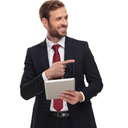 Photo for Portrait of curious and smiling businessman with tablet looking and pointing to side while standing on white background - Royalty Free Image