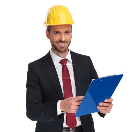 smiling businessman wearing a protection helmet holds blue files while standing on white background, portrait picture