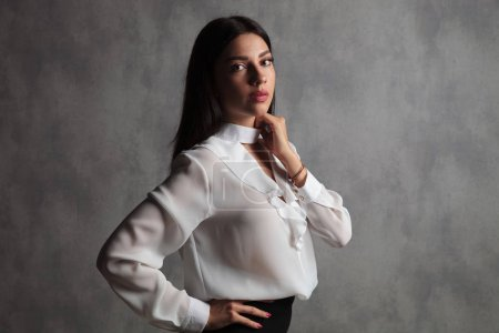 businesswoman standing with hnd on waist and neck while posing in studio