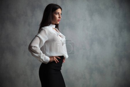 side view of a young businesswoman standing with hands on waist in studio