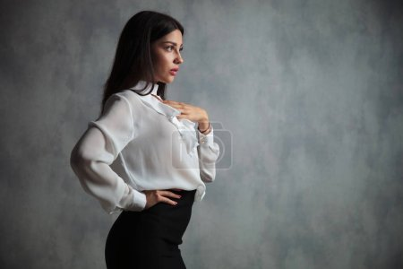 pensive businesswoman with hand on chest and waist standing and posing in studio