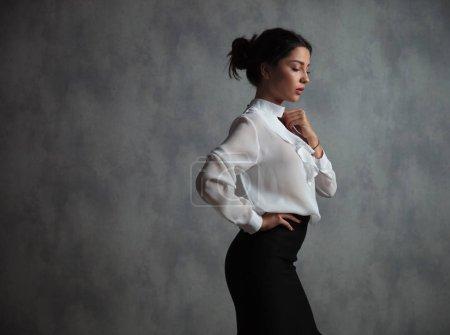 sad businesswoman standing in studio against grey background