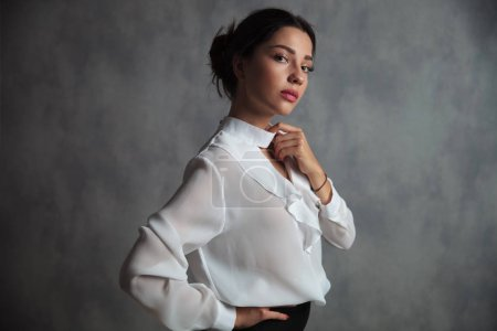 businesswoman holding her shirt's collar looks at the camera, studio picture
