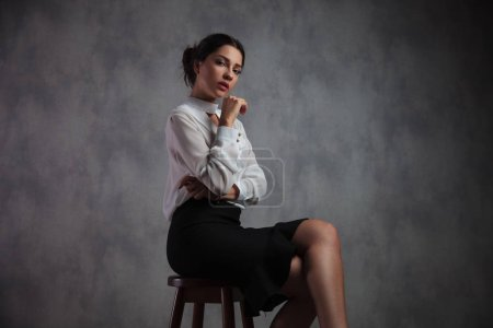 young businesswoman is thinking while sitting on a chair in studio