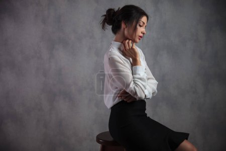 thoughtful or sad elegant woman is sitting on a stool in studio