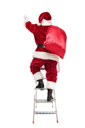 Photo pour Vue arrière du Père Noël étirant la main tout en montant l'échelle et debout sur fond blanc, image pleine longueur - image libre de droit