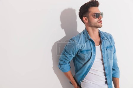 Photo for Attractive man standing against the wall and looking at a side wearing a pair of shades on a light background - Royalty Free Image