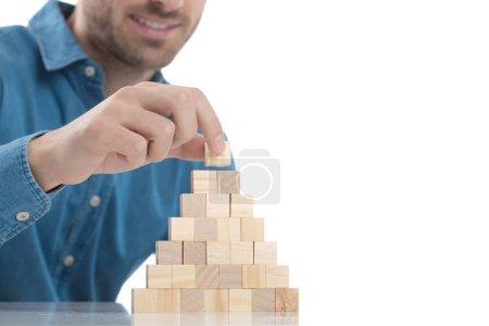 Photo pour Casual habillé homme plaçant très précisément une minuscule brique de bois sur le dessus - image libre de droit