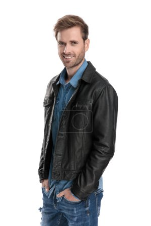 Photo for Charming casual man with black leather jacket is standing with his hands in pockets with wide smile on white studio background - Royalty Free Image