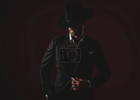 Photo for Attractive young man wearing tuxedo and black hat, looking down, holding hand in pocket, fixing coat and standing on black background, portrait - Royalty Free Image