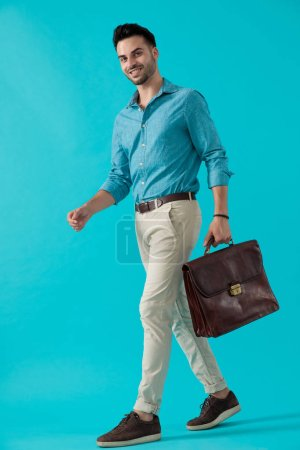 Photo for Side view of a beautiful casual man in blue shirt walking and carrying a briefcase with him happy on blue studio background - Royalty Free Image