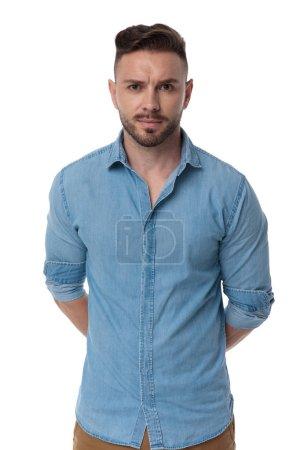 Photo pour Beau homme occasionnel avec chemise bleue est debout avec les mains derrière lui mystérieux sur fond de studio blanc - image libre de droit