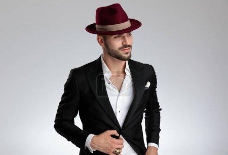 Photo pour Jeune homme d'affaires formel portant un costume noir, chapeau, anneau est debout et fixer sa veste avec une main dans la poche tout en regardant loin heureux sur fond de studio gris - image libre de droit