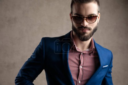 Photo for Close up of a beautiful formal business man wearing a navy suit and sunglasses standing and looking at camera with a strong attitude against gray studio background - Royalty Free Image