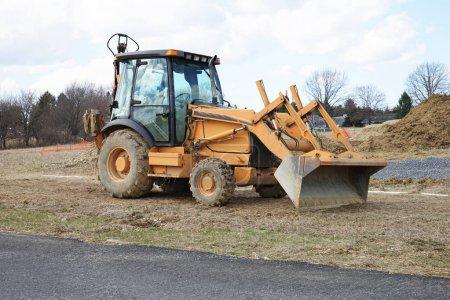 Photo pour Un chargeur frontal se trouve au ralenti près d'un chantier de construction . - image libre de droit