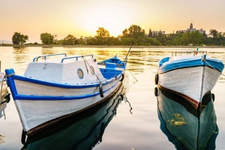 fishing boats in harbor of Sozopol on sunset background