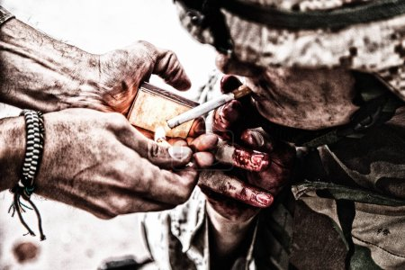 Photo for Wounded army soldier, tired military medics with fingers in blood, lighting cigarette with burning match in comrade palms. Psychological pressure, emotional trauma, post-traumatic disorder on war - Royalty Free Image