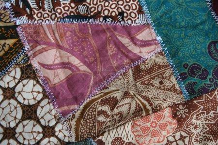 Photo pour Batik fond matériel, matériau indonésien reconstitué avec des points de zigzag blanc dans la conception de courtepointe folle dans les couleurs colorées bleu vert rose et brun - image libre de droit