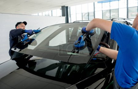 Photo for Automobile special workers replacing windscreen or windshield of a car in auto service station garage. - Royalty Free Image