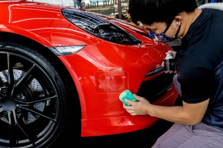 Photo for Car service worker applying nano coating on a car detail. Tools for polishing - Royalty Free Image