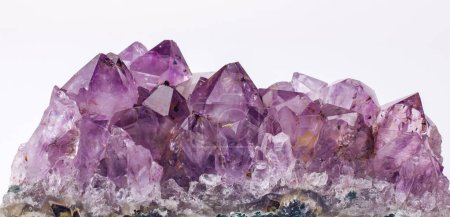 Purple rough Amethyst quartz crystals geode on whi...