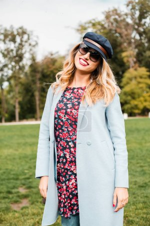 Attractive blonde woman wearing sunglasses and posing in park