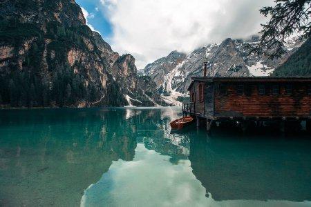 Photo pour Masse en bois avec cabane sur la côte du lac de montagne - image libre de droit