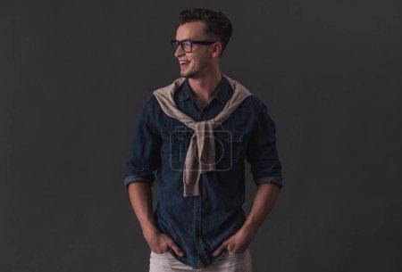 Foto de Atractivo joven en gafas es mirar lejos y sonriendo, sobre fondo gris - Imagen libre de derechos