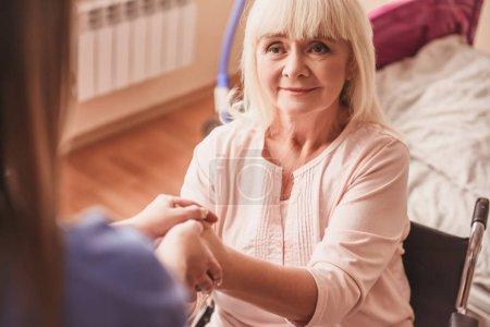 Photo pour Belle vieille dame tient la main du médecin et sourit tout en étant assis dans le fauteuil roulant dans la salle d'hôpital - image libre de droit