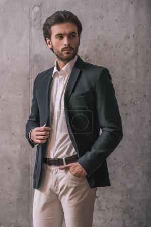 Photo pour Bel homme d'affaires confiant avec soies, en costume, regarde ailleurs, sur fond gris - image libre de droit