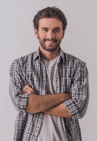 Photo for Handsome bearded man in casual clothes is looking at camera and smiling while standing with crossed arms on light background - Royalty Free Image