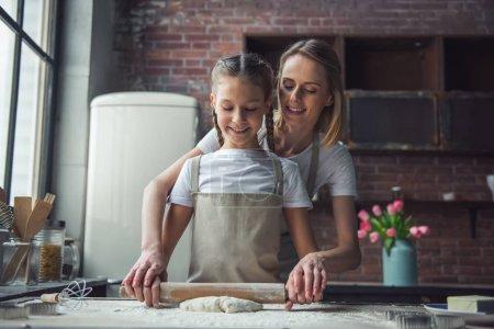 Photo pour Belle maman et sa fille en tabliers sont à l'aide du rouleau à pâtisserie et souriant tout en préparant la pâte à la maison - image libre de droit
