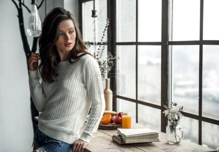 Photo pour Belle jeune fille en vêtements décontractés regarde par la fenêtre tout en s'appuyant sur une table en bois à la maison - image libre de droit