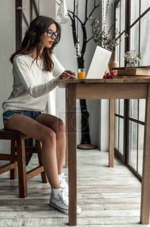 Photo pour Belle jeune fille en vêtements décontractés travaille avec un ordinateur portable tout en étant assis à la table en bois à la maison - image libre de droit