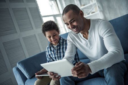 Photo for Happy Afro American father and son in casual clothes are using digital tablets and smiling while sitting on couch at home - Royalty Free Image